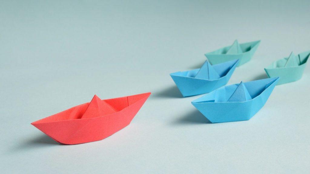 un bateau en papier guidant 4 autres